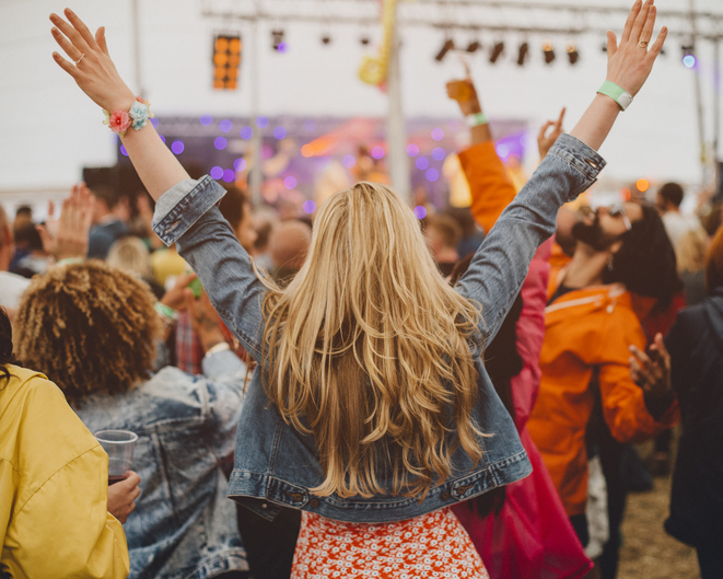 Young woman with blonde hair is dancing with her friends in a performance tent at a music festival. She has her arms outstretched and is watching the performance.